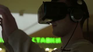 Close-up shot of a oung man in headphones getting experience in using VR-headset.