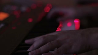 closeup man pianist hands play electric piano in night bar under flashes of colourful lights