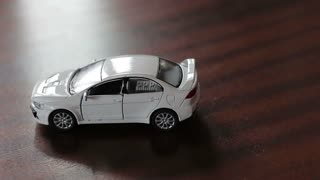 Collision of two toy cars. Accident of a white and gray car. Hitting in the back