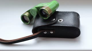 Composition: Vintage binoculars and carrying case. View through a magnifying glass