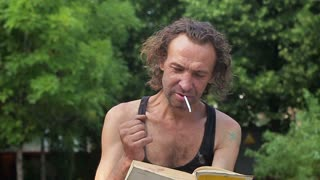 crazy homeless man smoking and reading book