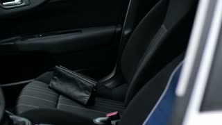 Crime concept, criminal thief stealing bag from parked car. Close up