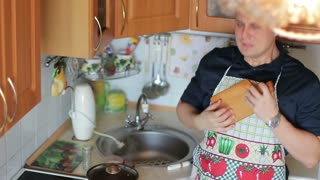 Cute cheerful positive guy sings and dances while cooking food in the kitchen.