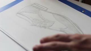 designer hand drawing a fashion sketch of shoes in details, close-up