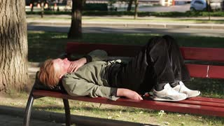 Drunk old homeless woman asleep on a bench in the city center