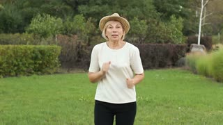 Elderly cheerful woman dancing on the street