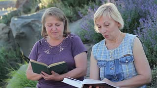 Elderly friends read books together on the street