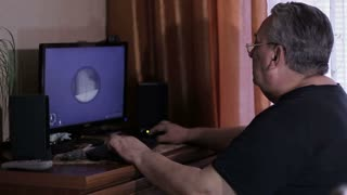 Elderly man playing online computer game at home