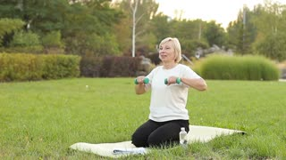 Elderly woman exercising outdoors with dumbbells