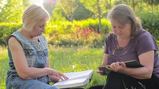 Elderly women reading books and discussing together