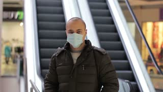 Epidemic. Man standing in a shopping center wearing a mask