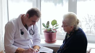 Family doctor talking with an old patient near the window