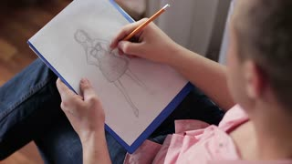 Fashion designer drawing a fashion sketch. The artist drawing with a pencil. Close-up