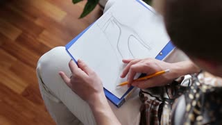 Fashion designer drawing a sketch of fashionable women's shoes