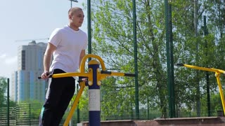 Fitness guy doing exercise on the waist in the street. Street workout