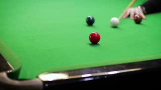 Force draw. Striking a ball on a snooker table, close-up