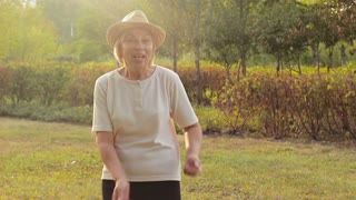 Funny elderly woman dances and laughs outdoors