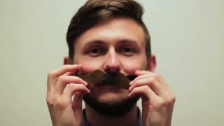 Funny guy writhes his face putting on his mustache