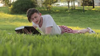 guy cheerfully reading a book out loud lying on the grass and commenting