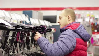Guy choosing a hair dryer in a home appliance store