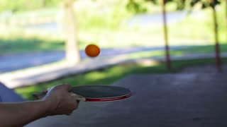 Hand holding a ping pong racket and stuffing a ball. close-up