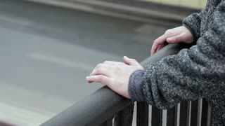 Hands of a suicide man on a bridge on a background of traffic cars