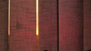 Hands opening the window blinds against the backdrop of the setting sun