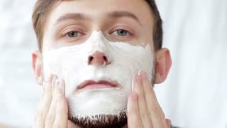 Handsome man applying a white clay mask