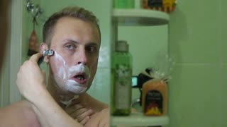 Handsome shirtless young man shaving his face.