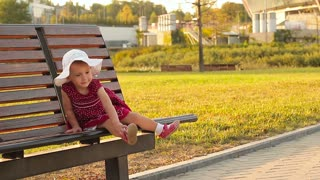 Happy little baby girl sitting on a bench in the park