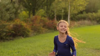 Happy little girl jumping and dancing on nature