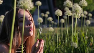 Happy sweet girl blows bubbles on the background of flowers. Close-up