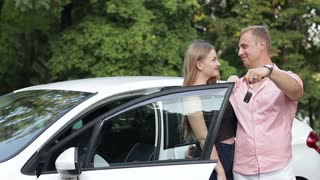 Happy young couple next to bought a new car. They are showing the keys and smiling