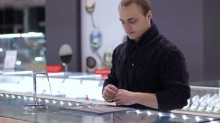 Jewelry shop. Young man chooses a bracelet