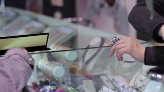 Jewelry store: adult woman tries on ring. Close up
