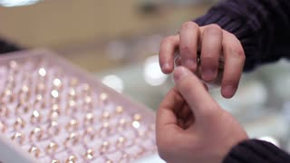 Jewelry store: Man tries on wedding ring. Close up