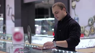 Jewelry store: Young Man tries on ring. Close up