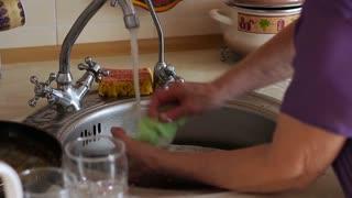 Kitchen. Elderly women washing dishes.