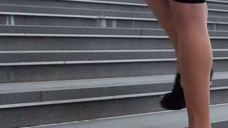 Legs and silhouette of young business woman. She climbs the stairs
