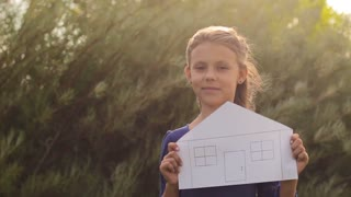 Little girl holding a house painted on paper