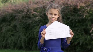 Little girl holding a model of a house. close-up