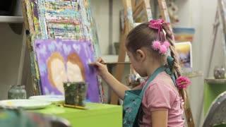 Little girl in art school paints a picture