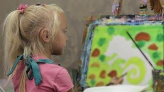 Little girl painter paints a picture. Art school