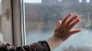 Lonely old woman looking out the window. Loneliness in old age