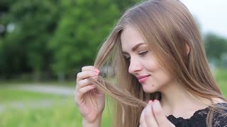 Lovely girl holding a lock of hair in her hands