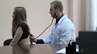 Male doctor checks patient's lungs using stethoscope. Close-up