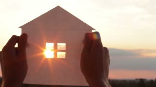 Male hands holding a paper house model against the sunset background