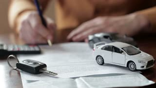 Male hands signing car insurance contract. concept: car insurance, car sales, garages, rental and alarm systems
