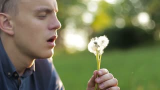 Man Blowing on a Dandelion, close-up
