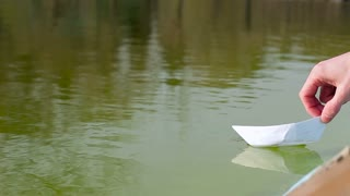 Man's hand putting paper boat on the water. Close up